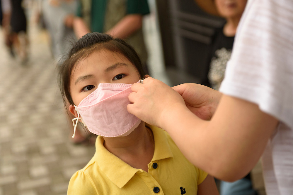 "A mother attaches a protective mask to her daughter's face in Busan, South Korea. The World Health Organization on Saturday called South Korea's MERS outbreak ""large and complex,"" as the country reported its 14th death from the virus. As of Saturday there were 138 confirmed cases, and thousands of those potentially exposed remained quarantined or in home isolation."