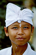Boy with rice on his face attending a Hindu ceremony at Pura Besakih, Bali's holiest temple at the slopes of Gunung Agung, the island's highest mountain and active volcano.