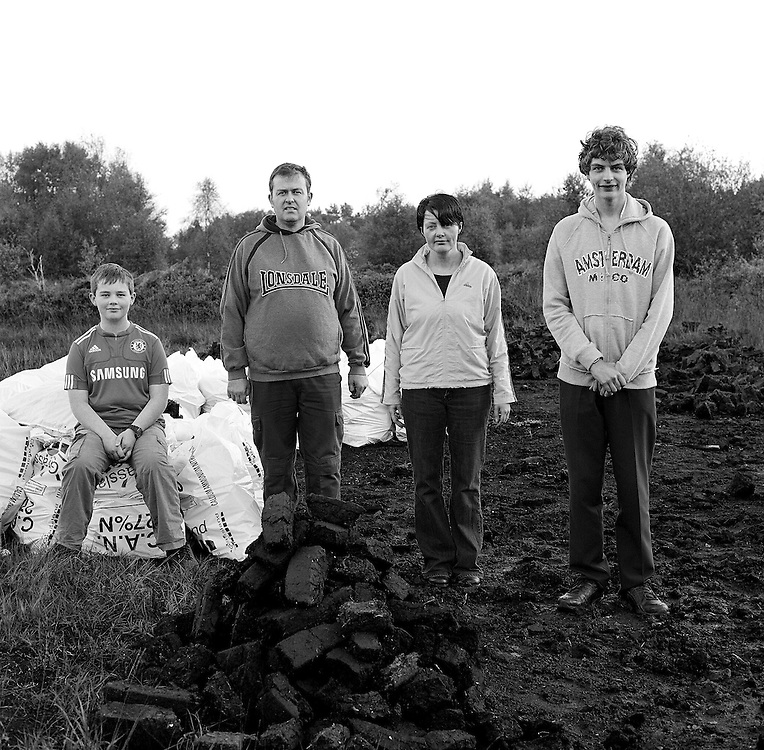 "Lynch Family. Leona & Mark with children Ruairí and Cormac on their turf bank at Mouds Bog. "" People are livid, we don't like being bullied. I bought a sláin in Achill in the Summer. If anyone tries to stop me, I'll bury the sleán in the middle of their head."""