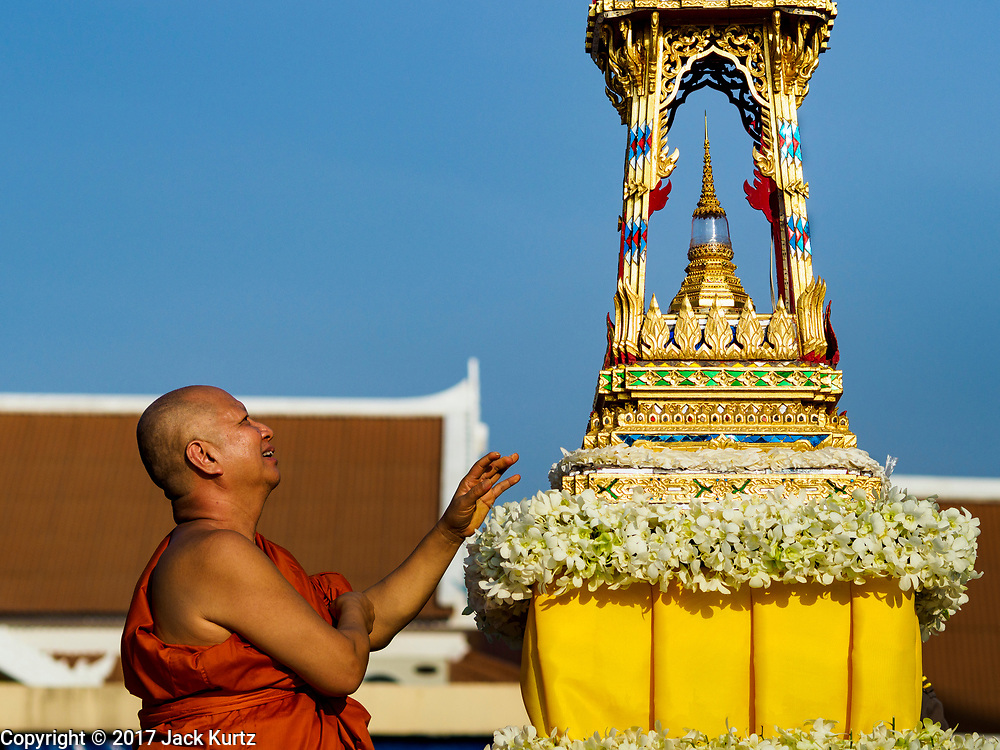 "03 NOVEMBER 2017 - BANGKOK, THAILAND: The abbot of Wat Prayurawongsawat on the Thonburi side of the Chao Phraya River, puts up a lantern for Loi Krathong. Loi Krathong is translated as ""to float (Loi) a basket (Krathong)"", and comes from the tradition of making krathong or buoyant, decorated baskets, which are then floated on a river to make merit. On the night of the full moon of the 12th lunar month (usually November), Thais launch their krathong on a river, canal or a pond, making a wish as they do so. Loi Krathong is also celebrated in other Theravada Buddhist countries like Myanmar, where it is called the Tazaungdaing Festival, and Cambodia, where it is called Bon Om Tuk.     PHOTO BY JACK KURTZ"