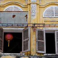 An aged yellow facade in Hoi An, Vietnam, reveals a traditional red paper lantern.
