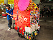 "10 AUGUST 2014 - BANGKOK, THAILAND: A volunteer pushes a cart full of joss paper to be burned in a merit making for Ghost Month at the Poh Teck Tung Shrine in Bangkok. The seventh month of the Chinese Lunar calendar is called ""Ghost Month"" during which ghosts and spirits, including those of the deceased ancestors, come out from the lower realm. It is common for Chinese people to make merit during the month by burning ""hell money"" and presenting food to the ghosts.     PHOTO BY JACK KURTZ"