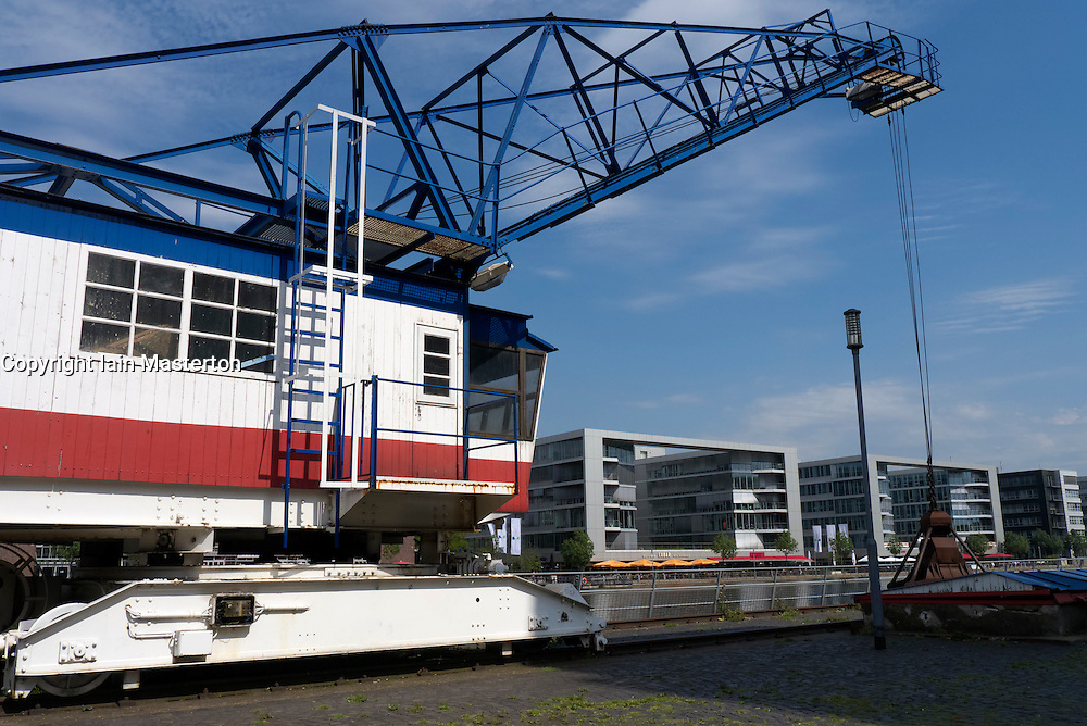 Old dock crane and new buildings to rear at Innenhafen area of Duisburg in North Rhine-Westphalia Germany