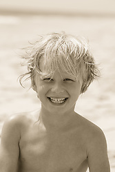 little blond boy smiling on the beach in East Hampton, NY