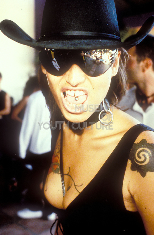 Clubber in cowboy hat and choker with tongue piercing sticking her tongue out, Space, Ibiza 1999