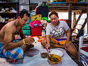 11 JULY 2017 - BANGKOK, THAILAND: A couple eats their lunch in a community built over the Chao Phraya River south of Krung Thon Bridge. The residents of the community expect to be evicted and their homes destroyed to make way for the city's plan to build a 14 kilometer long (22 mile) riverfront promenade. Thousands of families are expected to be evicted to accommodate the promenade. The riverside communities, built on stilts over the water, are prone to flooding and the city has been trying to control them for years. The houses are the only affordable housing for available to some of the poorest people in Bangkok.      PHOTO BY JACK KURTZ