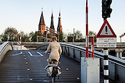 In Amsterdam worden fietsers gewaarschuwd voor een steile brug, waar aan het einde een scherpe bocht volgt.<br /> <br /> In Amsterdam a sign is warning cyclists for a steep bridge with on the end a sharp corner to the right.