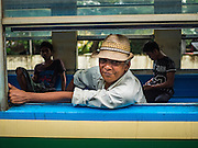 26 OCTOBER 2015 - YANGON, MYANMAR:  A man rides the Yangon Circular Train at the Pa Ywet Kone Station. The Yangon Circular Railway is the local commuter rail network that serves the Yangon metropolitan area. Operated by Myanmar Railways, the 45.9-kilometre (28.5 mi) 39-station loop system connects satellite towns and suburban areas to the city. The railway has about 200 coaches, runs 20 times daily and sells 100,000 to 150,000 tickets daily. The loop, which takes about three hours to complete, is a popular for tourists to see a cross section of life in Yangon. The trains run from 3:45 am to 10:15 pm daily. The cost of a ticket for a distance of 15 miles is ten kyats (~nine US cents), and for over 15 miles is twenty kyats (~18 US cents).    PHOTO BY JACK KURTZ