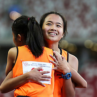 Raine Oh (#99) of Singapore Sports School shares a hug with team-mate Nurul Insyirah (#95) after the B Division girls' 100m final. (Photo © Lim Yong Teck/Red Sports)