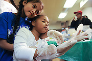 Amber Ayudtud, 7, helps Sienna Brown, 4, put on a pair of adult-sized latex gloves. The girls helped serve food to local victims of Hurricane Sandy at the Worship & Praise Community Church on Nov. 2, 2012, in the South Beach neighborhood of Staten Island, N.Y.