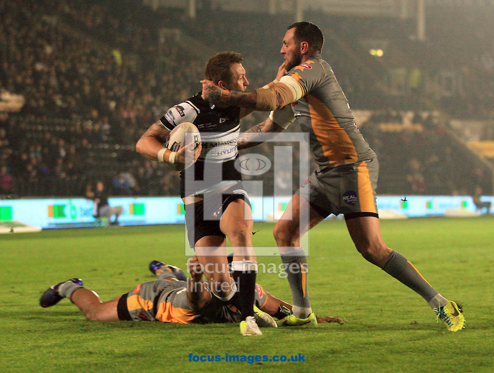 Jordan Rankin (ball) of Hull Football Club has a high shot hit on him by Gareth Hock of Salford Red Devils during the Tetley's Challenge Cup match at the KC Stadium, Kingston upon Hull<br />