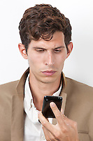 Pensive young man reading text message against white background