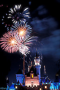 Sleeping Beauty Castle lit at night, fireworks, vertical