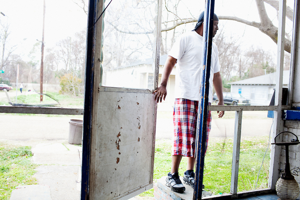 Jabari Wilson, 26, stands on the porch of the home he shares with his mother Ellen in the Baptist Town neighborhood of Greenwood, Mississippi on February 18, 2011.
