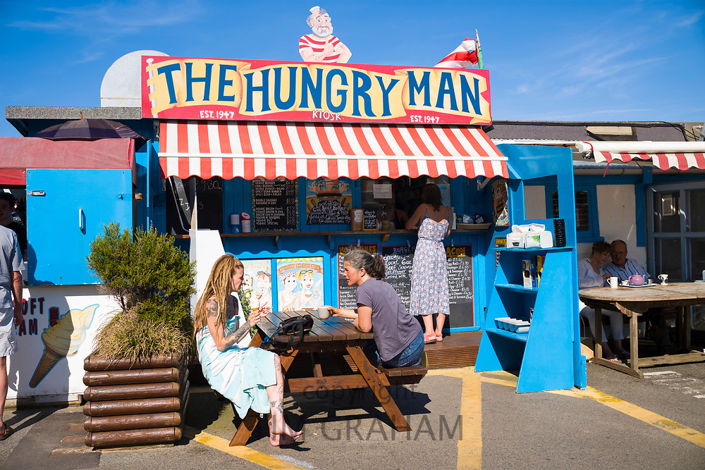 Holidaymakers at The Hungry Man food stall in the harbour at Rozel in St Martin region of Jersey, Channel Isles