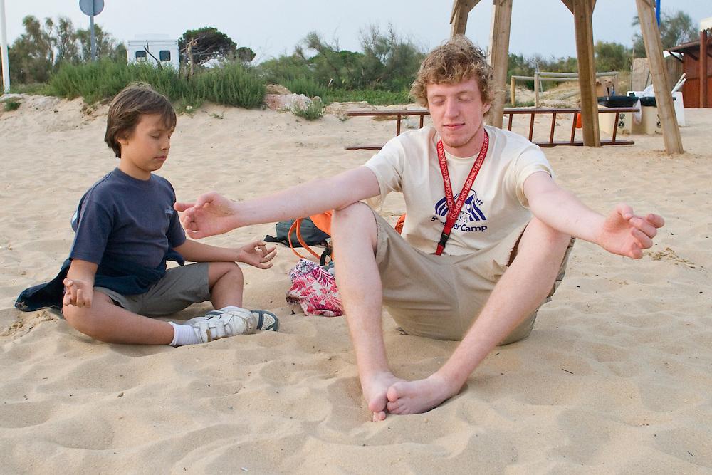 (El Puerto de Santa Maria, Spain - July 6, 2010) - Camper Ignacio teaches monitor Darren how to meditate during the sophomore (aged 6-9) beach barbecue in El Puerto. ..Photo by Will Nunnally / TECS