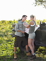 Couple by jeep woman adjusting man's shirt
