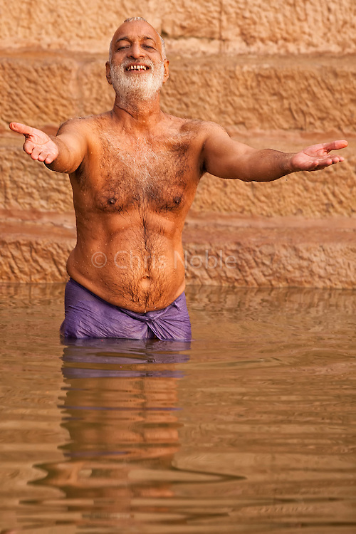A man sings to passing boats while performing his morning ritual puja by bathing in the Ganges River, Varanasi India.