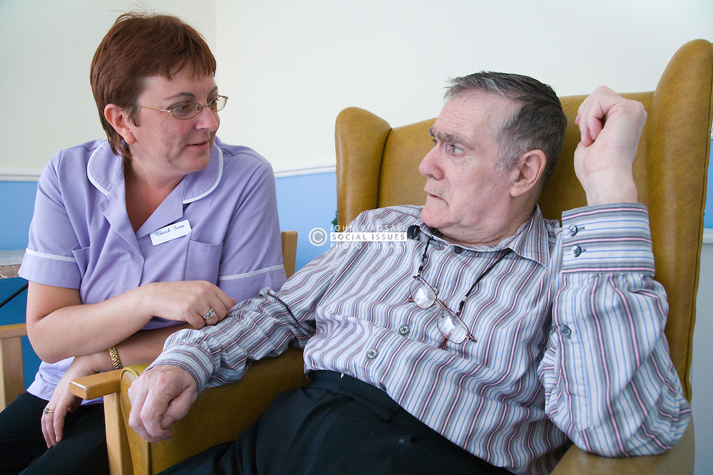 Care Assistant at Nursing Home chatting to man with Alzheimer's Disease,