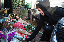 Highgate, London, December 26th 2016. Fans gather outside the London home of pop icon George Michael who died on Christmas day. PICTURED: A tearful woman lays flowers outside the gate of Michael's London home.