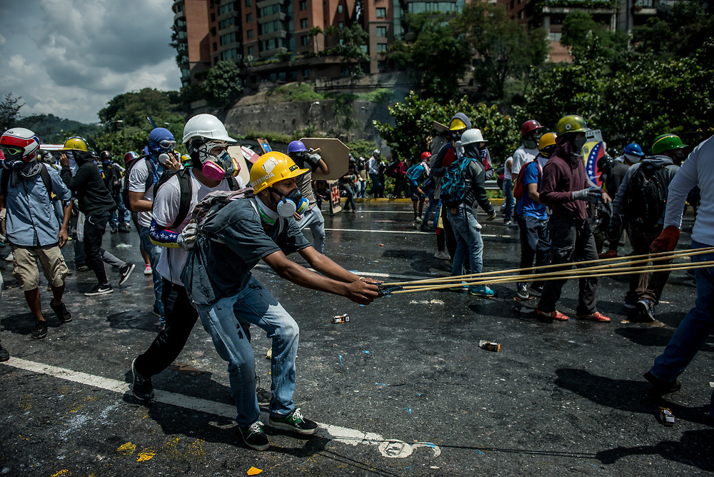 CARACAS, VENEZUELA - MAY 10, 2017:  Anti-government protesters use a giant slingshot to launch glass jars full of paint, and jars full of feces at members of the National Police who responded by heavily tear gassing and firing rubber bullets and buckshot at them. The streets of Caracas and other cities across Venezuela have been filled with tens of thousands of demonstrators for nearly 100 days of massive protests, held since April 1st. Protesters are enraged at the government for becoming an increasingly repressive, authoritarian regime that has delayed elections, used armed government loyalist to threaten dissidents, called for the Constitution to be re-written to favor them, jailed and tortured protesters and members of the political opposition, and whose corruption and failed economic policy has caused the current economic crisis that has led to widespread food and medicine shortages across the country.  Independent local media report nearly 100 people have been killed during protests and protest-related riots and looting.  The government currently only officially reports 75 deaths.  Over 2,000 people have been injured, and over 3,000 protesters have been detained by authorities.  PHOTO: Meridith Kohut