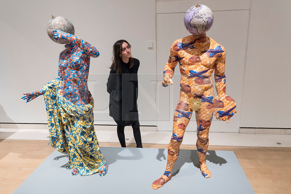 """© Licensed to London News Pictures. 07/12/2017. London, UK.  A staff member views (L to R) """"Discobolus (After Naukydes)"""", 2017, and """"The Townley Venus"""", 2017, both by Yinka Shonibare, RA, at a preview of """"From Life"""", a special exhibition at the Royal Academy examining what making art from life has meant to artists throughout history and how the practice has evolved as technology opens up new ways of creating artworks.  The exhibition runs 11 December to 11 March 2018.  Photo credit: Stephen Chung/LNP"""