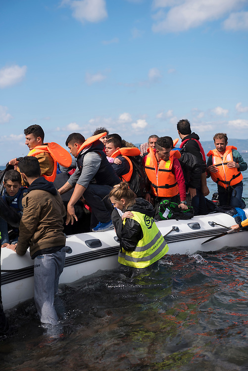A volunteer (in yellow vest) assists migrants out of their boat after landing on the Greek island of Lesbos, near the town of Skala Sikamineas. The coastline of Turkey is visible on the rightside of the photo.