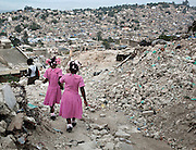 Schoolgirls return home in the hard hit Fort National neighborhood, one year after the earthquake.