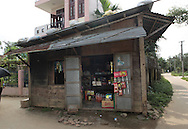 A drug store in the town of Phong Nam Village. The house in the background is the largest in the village and belongs to the town doctor.  Photograph by Dennis Brack
