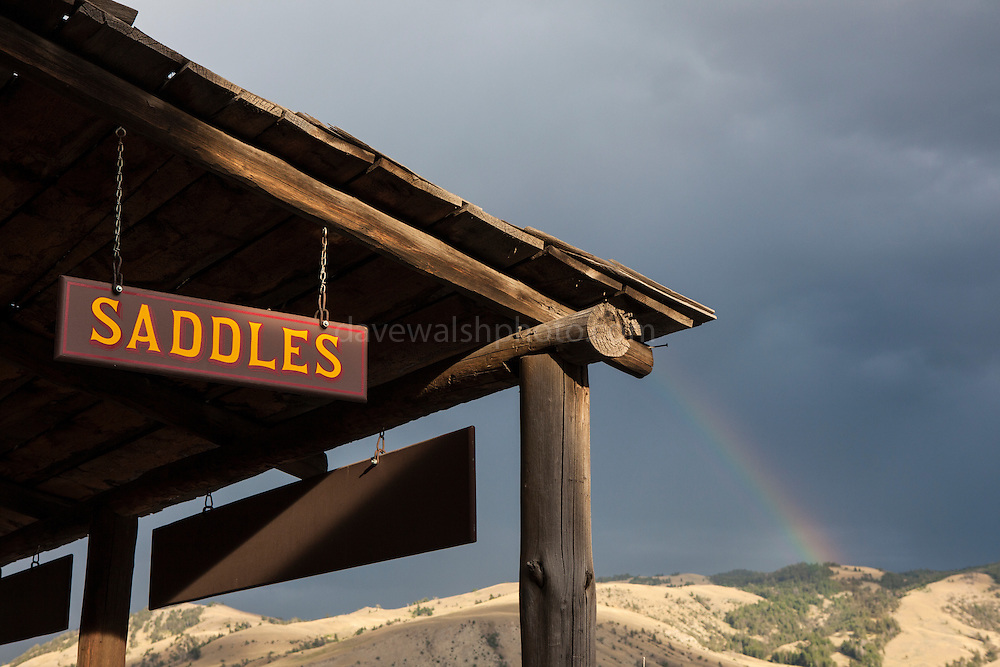 Shop sign in Gardiner, Montana, the north west gateway town to Yellowstone National Park, with a rainstorm commencing in the background.