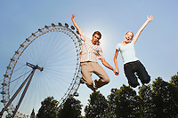 Young couple in park jumping in air in front of London Eye portrait low angle view