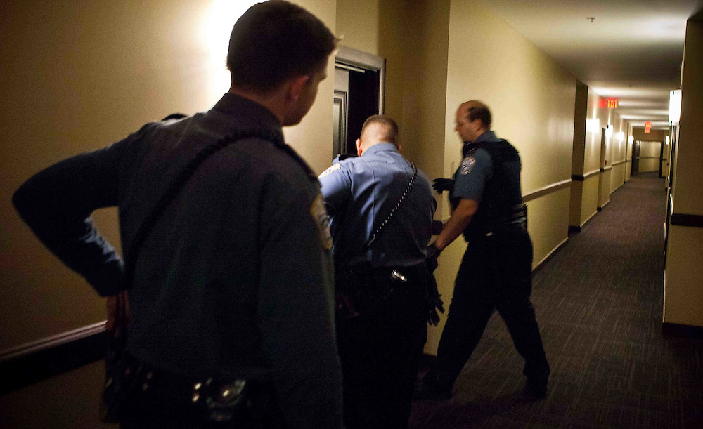Arlington Police Officer Constantine Rallis and two other officers try to check on the well being of a woman in an Arlington apartment building.  The woman's boyfriend had told police she was threatening to commit suicide.   Photo by Ed Buice