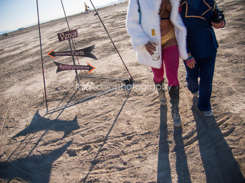 Burners walk home at dawn, carrying an empty bottle past a street sign to Venus, on the Playa at Burning Man.