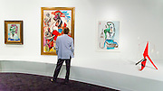 Man studies a Picasso painting with an Alexander Calder mobile at right, at Art Basel Miami Beach 2015