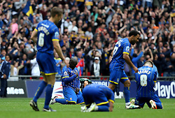 Adebayo Akinfenwa of AFC Wimbledon drops to his knees after his side clinch promotion to League One - Mandatory by-line: Robbie Stephenson/JMP - 30/05/2016 - FOOTBALL - Wembley Stadium - London, England - AFC Wimbledon v Plymouth Argyle - Sky Bet League Two Play-off Final