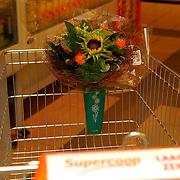 NLD/Huizen/20050713 - Supermarkt Supercoop heeft aan de winkelwagen een houder voor een bosje bloemen gemonteerd.winkelkar, winkelen, gemak,
