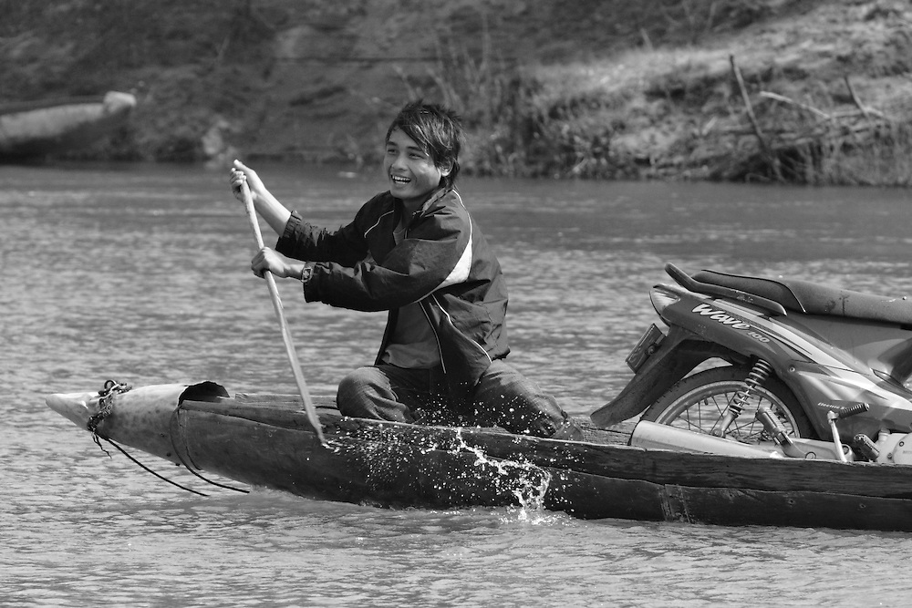 """A young man pilots a """"bomb boat"""" across the Senphen tributary of the Bangphai River, outside the """"bomb village"""" of Ban Senphen. The village is located in the Ban Phanhop valley, one of the """"chokes"""", or narrow corridors along the Ho Chi Minh Trail in Laos that were heavily bombed by American forces during the Vietnam War. Villagers say the boat, made of aluminum, was likely a fuel cannister from a War-era American plane."""