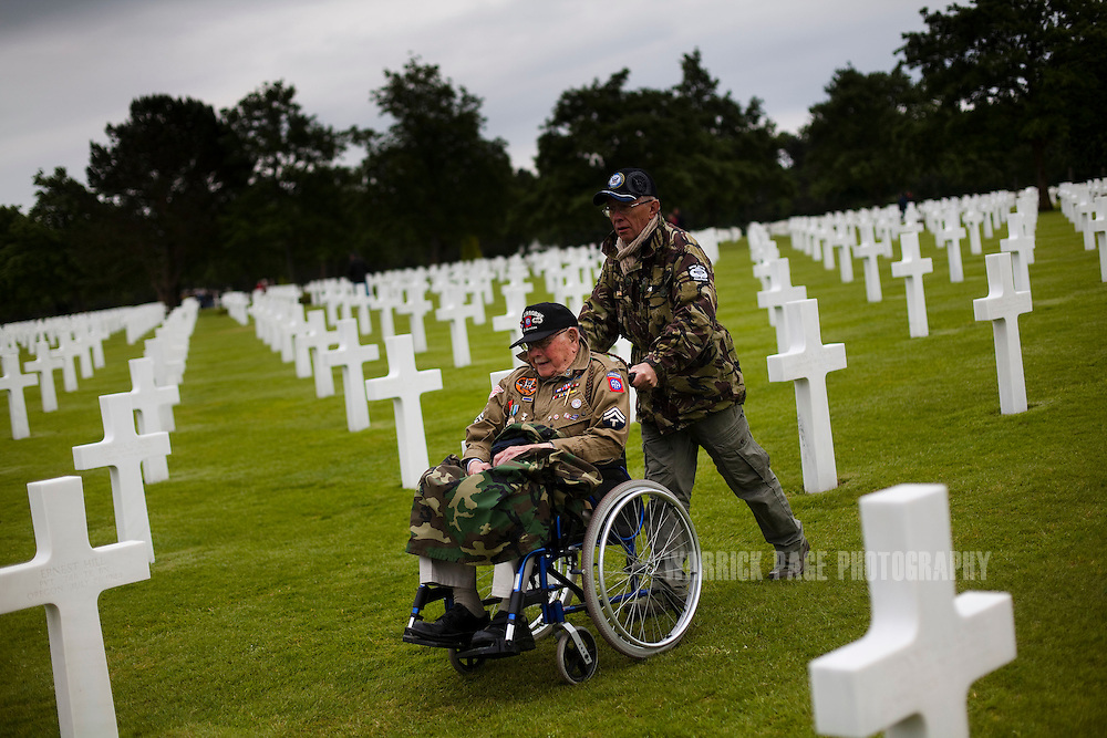 WWII Veteran Earl Geoffrian is wheeled through the US cemetery by a former French paratrooper on June 5, 2012, in Colleville-sur-Mer, France. Normandy is the only place in the world that has seen a consistent mass-pilgrimage of war veterans returning to the lands where they fought. No other lands that have born witness to war - including other WWII battlefields - have drawn veterans back in the way that Normandy has. Along with the veterans come thousands of WWII historical enthusiast and family members of passed veterans. Sixty-eight years on the numbers of veterans returning to the beaches and fields where they fought dwindle, as age and time prevail. (Photo by Warrick Page)