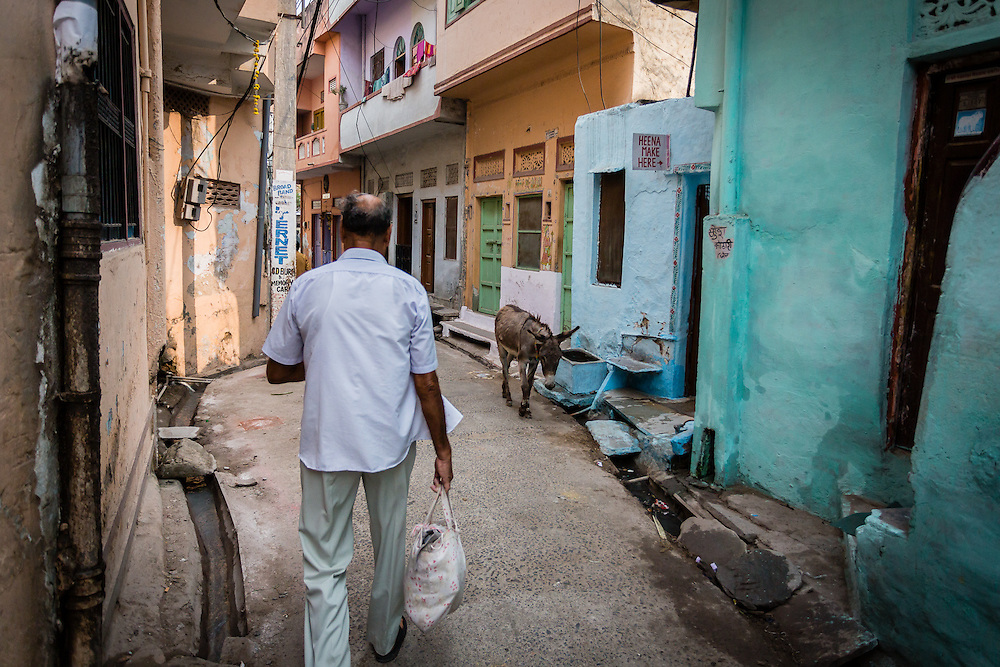 Johan, a retired teacher, walks back home through the streets of Udaipur, after a morning bath in Hanuman Ghat, in Lake Pichola.