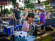"30 MARCH 2013 - BANGKOK, THAILAND:  A woman works at her sewing stand on Sukhumvit Road in Bangkok while a tourist walks by her. Thailand's economic expansion since the 1970 has dramatically reduced both the amount of poverty and the severity of poverty in Thailand. At the same time, the gap between the very rich in Thailand and the very poor has grown so that income disparity is greater now than it was in 1970. Thailand scores .42 on the ""Ginni Index"" which measures income disparity on a scale of 0 (perfect income equality) to 1 (absolute inequality in which one person owns everything). Sweden has the best Ginni score (.23), Thailand's score is slightly better than the US score of .45.  PHOTO BY JACK KURTZ"