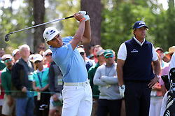 April 6, 2018 - Augusta, GA, USA - Rickie Fowler hits his tee shot on the fourth hole as Phil Mickelson watches during the second round of the Masters at Augusta National Golf Club on Friday, April 6, 2018, in Augusta, Ga. (Credit Image: © Curtis Compton/TNS via ZUMA Wire)