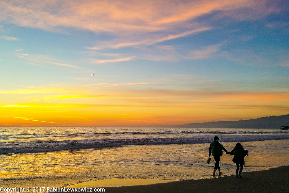 a couple walk along the santa monica beach shoreline on wednesday, december 27, 2017.
