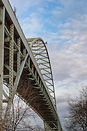 Picture of the Fremont Bridge, taken from west side of the Willamette River, with a blue sky above it.
