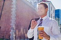 Portrait of mature businessman walking while holding a cup of coffee