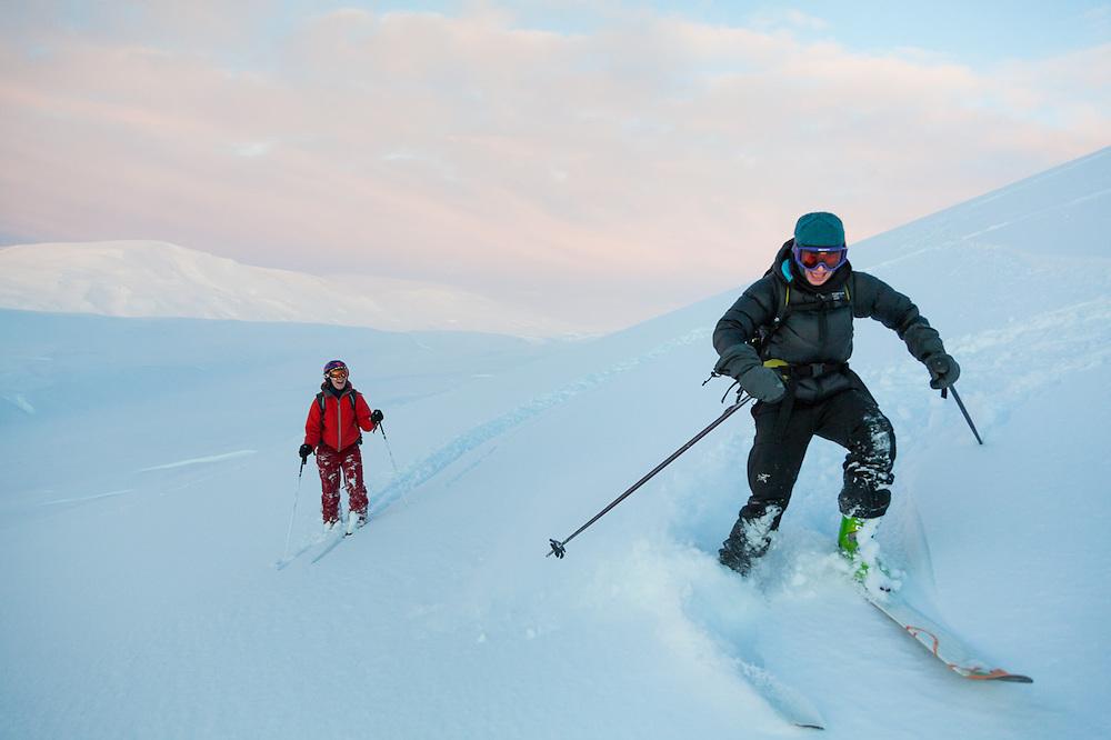 Michelle Blade (left) and Kiya Riverman ski down Hallwylfjellet, Svalbard at sunset.