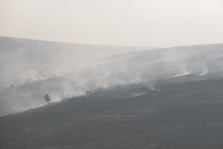 "© Licensed to London News Pictures . 28/06/2018 . Saddleworth , UK . A view of Saddleworth Moor shrouded in smoke , as viewed across Higher Swineshaw Reservoir . The army are being called in to support fire-fighters , who continue to work to contain large wildfires spreading across Saddleworth Moor and affecting people across Manchester and surrounding towns . Very high temperatures , winds and dry peat are hampering efforts to contain the fire , described as "" unprecedented "" by police and reported to be the largest in living memory . Photo credit: Joel Goodman/LNP"