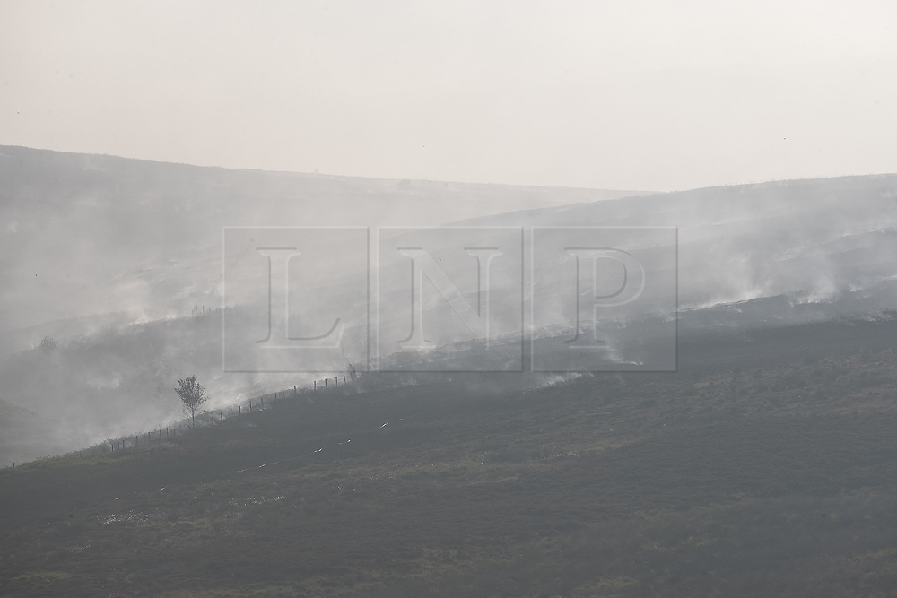 """© Licensed to London News Pictures . 28/06/2018 . Saddleworth , UK . A view of Saddleworth Moor shrouded in smoke , as viewed across Higher Swineshaw Reservoir . The army are being called in to support fire-fighters , who continue to work to contain large wildfires spreading across Saddleworth Moor and affecting people across Manchester and surrounding towns . Very high temperatures , winds and dry peat are hampering efforts to contain the fire , described as """" unprecedented """" by police and reported to be the largest in living memory . Photo credit: Joel Goodman/LNP"""