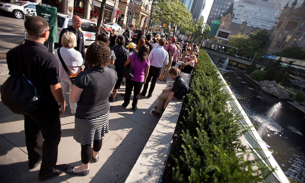 Toronto, Ontario ---11-08-27--- Hundreds of people lime up outside Roy Thomson Hall August 27, 2011, to obtain tickets for the state funeral for late NDP leader Jack Layton.<br /> AFP/GEOFF ROBINS/STR