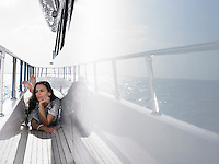 Young woman lying on deck of yacht