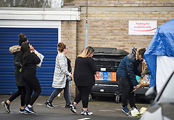 © Licensed to London News Pictures. 08/04/2019. London, UK. An emotional group of people place flowers at the scene where a woman in her 20's was found dead after reportedly falling form a top floor window at Brookbank flats on Turkey Street, in Enfield, North London. A man was arrested nearby on suspicion of murder. Photo credit: Ben Cawthra/LNP